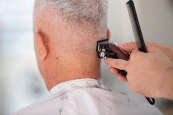 person cutting hair with cordless hair clippers