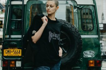 Woman with shaved head standing neat black vehicle