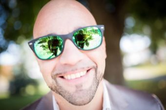 Bald adult with sunglasses smiling