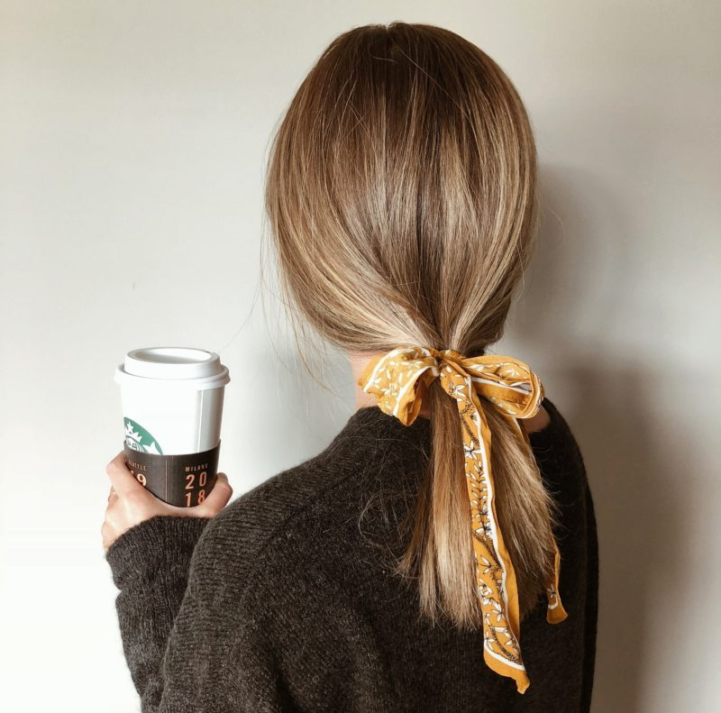 Woman in black sweater holding a coffee cup