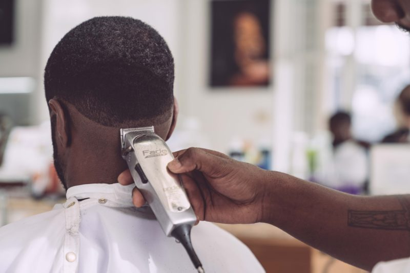 person holding hair clipper cutting the hair of man sitting