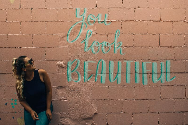 woman by a wall that reads ''you look beautiful''
