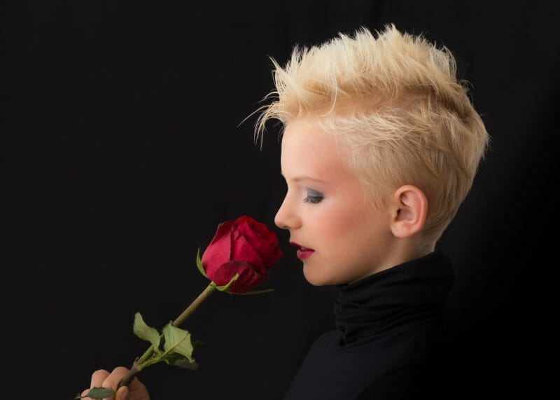Person with a pixie cut smelling a rose on a black background
