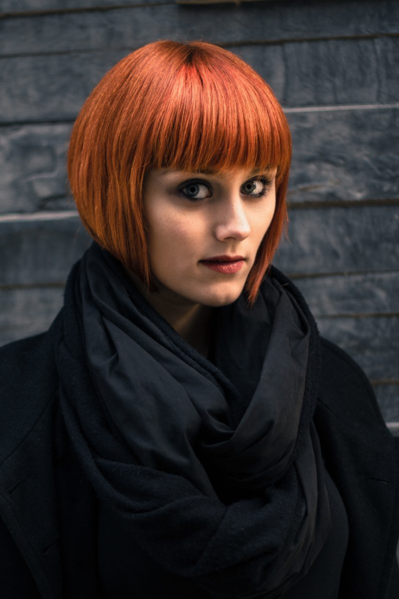 red hair in short blunt bob with bangs and dark clothes