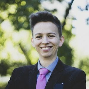 white transmasculine person in suit smiling