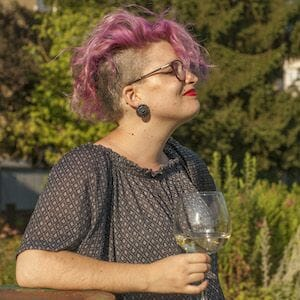 pink-haired femme white person with an undercut holding a glass of white wine